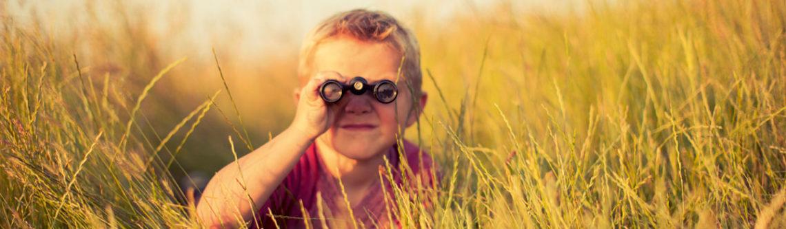 Junge mit Fernglas im Gras